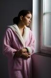 Muchacha triste enferma hermosa en los pijamas que miran a través de ventana del hospital Imagen de archivo libre de regalías