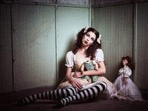Muchacha triste extraña con las muñecas que se sientan en lugar abandonado Foto de archivo