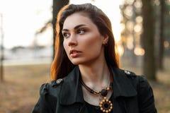 Muchacha triste hermosa con un rasgón en el parque en la puesta del sol Imagen de archivo libre de regalías