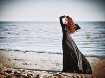Muchacha triste hermosa del goth que se coloca en la playa del mar Fotos de archivo