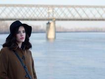 Muchacha triste hermosa en capa y sombrero clásicos al lado del río Fotos de archivo libres de regalías