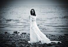Muchacha triste hermosa en el vestido blanco que se coloca en costa de mar Foto de archivo