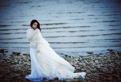 Muchacha triste hermosa en el vestido blanco que se coloca en orilla de mar Imágenes de archivo libres de regalías