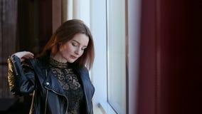Muchacha triste hermosa en una chaqueta de cuero que se coloca cerca de la ventana metrajes