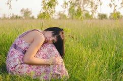 Muchacha triste hermosa que se sienta solamente en el prado en verano Imagen de archivo libre de regalías