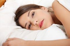 Muchacha triste joven que miente en cama. Imagenes de archivo