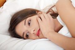 Muchacha triste joven que miente en cama. Fotos de archivo