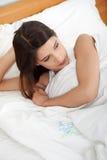 Muchacha triste joven que miente en cama. Foto de archivo