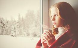 Muchacha triste pensativa con una bebida que se calienta que mira hacia fuera la ventana adentro Imagen de archivo