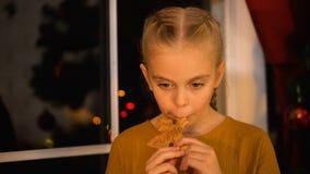 Muchacha triste que come la galleta de Navidad, colocándose cerca de ventana, organización huérfana de la caridad almacen de metraje de vídeo