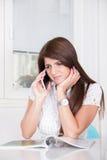 Muchacha triste que habla en el teléfono en casa Fotografía de archivo