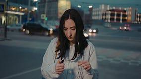 Muchacha triste que intenta encender la bengala con el encendedor de gas, delante del tráfico de ciudad de la noche borroso metrajes