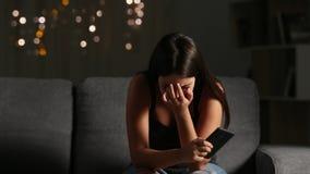Muchacha triste que lee el mensaje de teléfono que tiraniza cibernético metrajes
