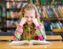 Muchacha triste que lee un libro en la biblioteca Fotografía de archivo libre de regalías