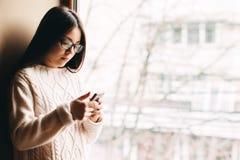 Muchacha triste que manda un SMS en la ventana Imágenes de archivo libres de regalías