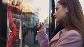 Muchacha triste que mira en la ventana de la tienda, soñando con el vestido costoso, ventas y descuento almacen de metraje de vídeo