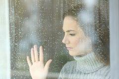 Muchacha triste que mira a través de una ventana en un día lluvioso Imagen de archivo libre de regalías