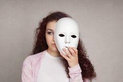 Muchacha triste que oculta detrás de máscara Fotos de archivo