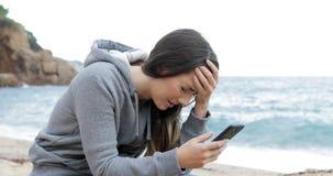 Muchacha triste que recibe malas noticias en línea en la playa almacen de metraje de vídeo