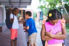 Muchacha triste que se coloca en el pasillo de la escuela Imágenes de archivo libres de regalías