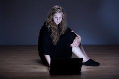 Muchacha triste que se sienta con el ordenador portátil Fotos de archivo