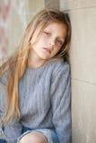 Muchacha triste que se sienta contra la pared Imagen de archivo libre de regalías