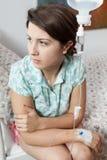 Muchacha triste que se sienta en cama en hospital Fotos de archivo libres de regalías