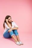Muchacha triste que se sienta en el piso que parece abajo aislado en rosa Fotografía de archivo libre de regalías
