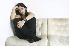 Muchacha triste que se sienta en el sofá Imagenes de archivo