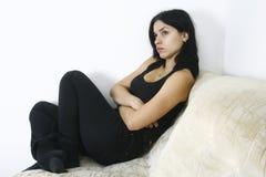 Muchacha triste que se sienta en el sofá Imagen de archivo