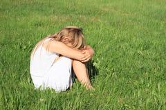 Muchacha triste que se sienta en hierba Imagenes de archivo