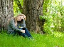 Muchacha triste que se sienta en hierba y que lee un libro Fotos de archivo