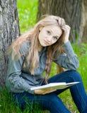 Muchacha triste que se sienta en hierba y que lee un libro Fotos de archivo libres de regalías