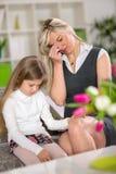 Muchacha triste que se sienta en la mamá preocupante siguiente del sofá imagenes de archivo