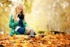 Muchacha triste que se sienta en las hojas de otoño Fotos de archivo libres de regalías