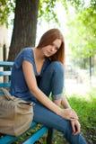 Muchacha triste que se sienta en un banco de parque Imagenes de archivo