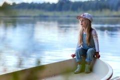 Muchacha triste que se sienta en un barco el día de verano del lago Imagenes de archivo