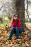 Muchacha triste que se sienta en un parque Foto de archivo libre de regalías