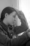 Muchacha triste que se sienta en un travesaño de la ventana en la depresión Foto de archivo