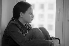 Muchacha triste que se sienta en un travesaño de la ventana en la depresión Fotos de archivo libres de regalías