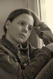 Muchacha triste que se sienta en un travesaño de la ventana en la depresión Imágenes de archivo libres de regalías