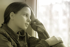 Muchacha triste que se sienta en un travesaño de la ventana en la depresión Fotografía de archivo libre de regalías