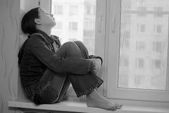 Muchacha triste que se sienta en un travesaño de la ventana en la depresión Fotografía de archivo