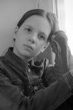 Muchacha triste que se sienta en un travesaño de la ventana en la depresión Foto de archivo libre de regalías