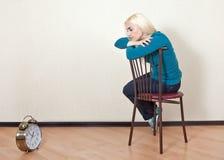 Muchacha triste que se sienta en una silla y miradas en la suya reloj Imágenes de archivo libres de regalías