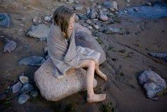 Muchacha triste que sienta en las rocas la playa envuelta en una toalla Fotos de archivo libres de regalías