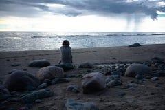 Muchacha triste que sienta en las rocas la playa envuelta en una toalla Foto de archivo