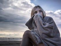 Muchacha triste que sienta en las rocas la playa envuelta en una toalla Fotografía de archivo