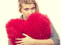 Muchacha triste que sostiene la almohada roja grande en forma del corazón Imagenes de archivo