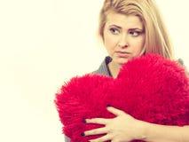 Muchacha triste que sostiene la almohada roja grande en forma del corazón Imagen de archivo